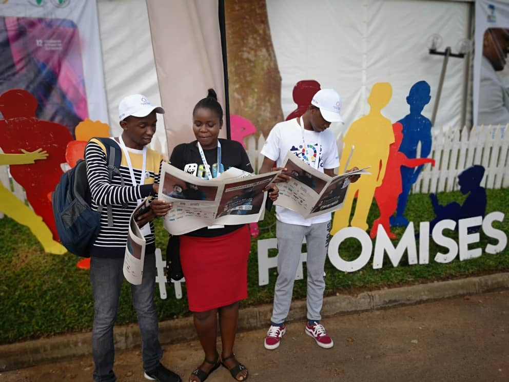 Three people read 17Promises in front of the 17Promises display